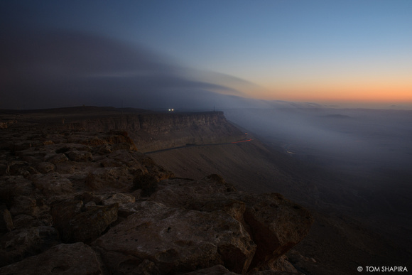 Landscape image showing fog rolls into the Ramon Crater at dawn.