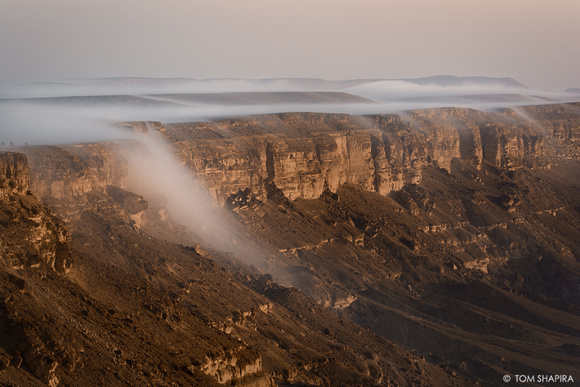 Landscape image showing fog-waterfalls on the edge of the Ramon Crater, Israel.